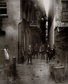 Pennington Street, Wapping, December 1906. This long range of late 17th century dwellings stood directly opposite the towering walls and warehouses of London Docks, which they pre-dated.