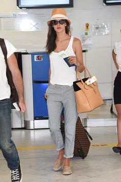 Airport Chic 101: Travel Style Stars. Alessandra Ambrosio.  Ambrosio proves dressing for comfort can still look totally chic, wearing a tank, striped chinos by Big Star, a woven hat and suede espadrilles as she flew into sunny Cannes.