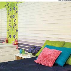 No quarto de uma adolescente, a cabeceira da cama foi feita com lambris. Alguns deles, na parte inferior, receberam tinta em degradé de roxo e lilás. Projeto do escritório CSDA Interiores.