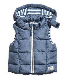 Denim blue. Padded vest with a detachable hood, stand-up collar, and zip at front.