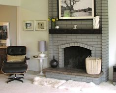 Painted brick fireplace in a light gray with dark wood mantel in a ...