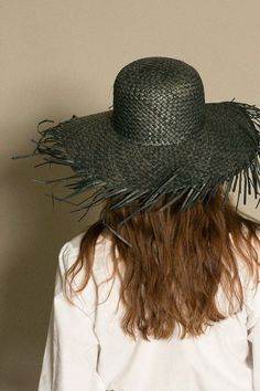 8e704884ab51f Woven wide brim straw hat with an exaggerated fray edge. Available in both  black and gold straw.
