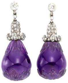 A Pair Of Antique Carved Amethyst And Diamond Earrings.    Ccirca 1890.  A pair of antique amethyst and diamond earrings, each earring with a carved amethyst drop suspended from a pave rose-cut diamond cupola drop and single collet top, mounted in silver and gold. Listing via 1stdibs.