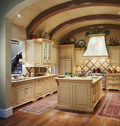 Lightly  Glazed Cabinets - With its beamed and barrel-arched  ceiling, this kitchen provides space and functionality without sacrificing style. The wooden cabinets are lightly glazed to match the  cream granite countertops. Neutral hues allow for more dynamic patterns and  accent colors, like the glazed pots on top of the cabinets.