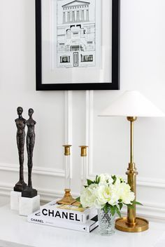 Modernist bronze sculpture, brass lucite candlesticks, Visual Comfort Hargett brass table lamp, antique architecture print, Chanel coffee table books, living room styling