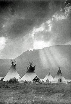 Blackfoot encampment under clouds,