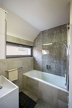 Okenní rámy, dlažby a obklady v celém domě drží jednotnou neutrální šedou linii
