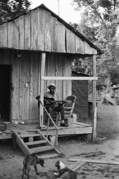 Scott Dunbar playing guitar on his porch, Lake Mary, Mississippi 1968. photo by William R. Ferris