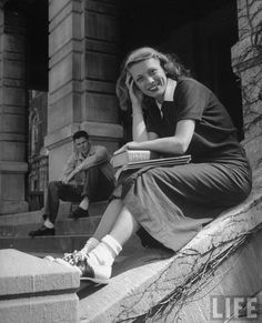 Portrait of Jane Stone with her book and notebooks. Her boyfriend is sitting in the background. Both are students at the Univ. of Missouri. LIFE, April 1949. Photographer: Peter Stackpole.