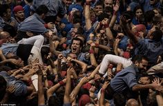 A team in blue look elated as they celebrate forming their human tower in the Concurs de Castells