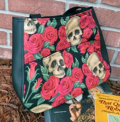 """Skull and Roses Ethel Tote  A roomy, sturdy and stylish open tote bag. With a teardrop shape, Ethel veers away from the usual boxy tote. It's a """"stuff it in and run out the door"""" kind of bag, designed to comfortably sling over your shoulder. There are open pockets with magnetic closures on the outside and a zippered pocket inside for the small things."""