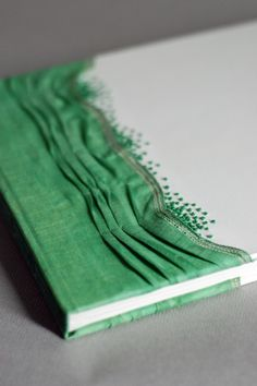 I like the detailing of the fabric and the beads.  This can be done with the sewing that allows the book to lay flat open.