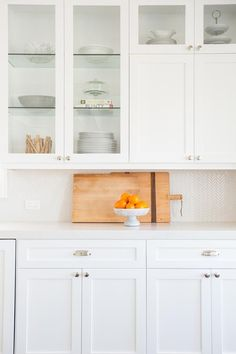 Amazing white kitchen features creamy white shaker cabinets paired with a white marble like quartz ...