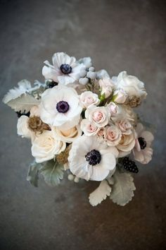 my favorite flower anemones- white Anemones with black centers bridal boquet. Add a hint of baby's breath. Keep the dusty miller and grey berry, blush and cream roses. Stems wrapped in light grey satin ribbon or placed in a silver holder with grey or grey blue satin ribbon bow and add a hanging silver ampersand charm. make it sparkle with rhinestones.