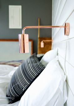 This copper wall light adds a gorgeous accent to this scandinavian bedroom interior.