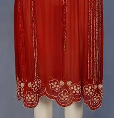 DECO BEADED CHIFFON DRESS. Sleeveless cranberry silk decorated in iridescent white and red beaded floral, having scalloped low waist with long, wide chiffon fringe, slightly gathered skirt with scalloped hem. Detail