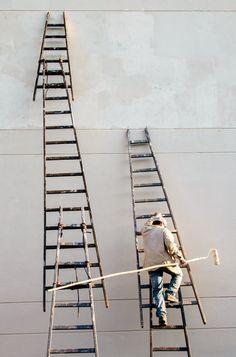 Мужчина карабкается по лестнице, прислоненной к стене здания
