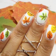 Add creativity to your nails with this multi colored leaf themed fall nail art design.