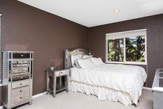 Warm cocoa walls and metallic/mirrored bedroom furniture