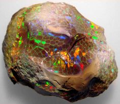 Famous Mezezo rough cut opal by J.P. Gier — Opal was first discovered in Mezezo, Shewa province in Ethiopia in the early 1990s. Many of the Mezezo opals have a darker body color, tending to orange to red to chocolate brown. There are two type of Ethiopian opals one is the Chocolate type called Mezezo and the other is Welo, smaller rough has unlike Mezezo little or no matirix.