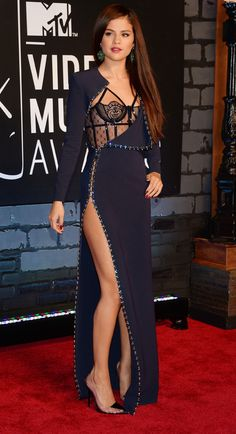 Selena Gomez at MTV VMAs 2013 with a sexy dress that looks like it's peeling away to reveal a lacy structured cage-like bustier underneath and a high thigh-revealing slit at the side of the skirt.