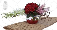 Orchids create horizontal interest in this Valentine arrangement of red roses. Wood twigs and red acrylic nuggets in a glass bowl create a unique style. #PennockFloral