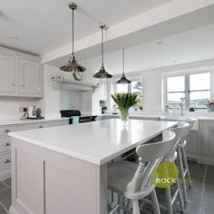 An open-plan kitchen featuring the Bianco Marmo Suprema style quartz. It features grey and white tones within and lots of space. A perfect island sits in the middle for the perfect dinner parties. It is also a handmade kitchen.