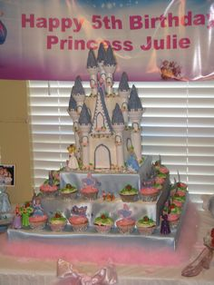 First castle cake that I made.  We handmade the cupcake stand with satin cloth and pearls.  The cupcakes were pumpkins and cinderella items.  Cake was white with homemade buttercream icing with MM fondant accents