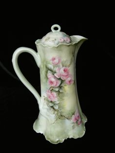 """stunning antique Limoges porcelain hand painted chocolate pot with the sweetest pink cabbage roses! The soft roses and foliage cascade all around this piece and there are even roses on the lid.    It is signed by the artist """"Skiff"""", on the bottom. Background colors are light greens, cream, and a bit of blue.    The original mold has lots of relief detail and a ruffled foot.    It is marked Haviland France Limoges Mark 12, this dates it 1894 to 1931."""