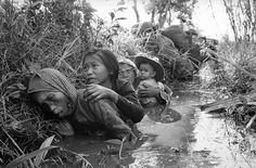 In this Jan. 1, 1966 file photo, women and children crouch in a muddy canal as they take cover from intense Viet Cong fire at Bao Trai, about 20 miles west of Saigon, Vietnam.