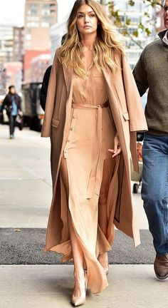Gigi Hadid wears a silk maxi dress by Self Portrait with a camel coat and nude heels