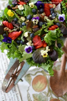 Salad of baby greens, blueberries, strawberries, gorgonzola, candied pecans with violas, served in a wheelbarrow with spade servers (from Pottery Barn)
