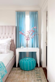 Quaint contemporary bedroom featuring light gray and turquoise colors on a bed and surrounding furnishings.