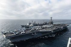 USS John C. Stennis (CVN 74) participates in a replenishment-at-sea with the fast combat support ship USNS Rainier (T-AOE 7) and the guided-missile cruiser USS Mobile Bay (CG 53).