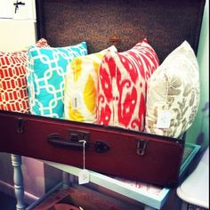 Handmade cushions in bright fabrics. And i love that trunk!