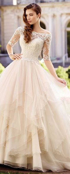 This off-the-shoulder tulle ball gown with lace three-quarter length sleeves features asymmetrically tiered and layered full skirt, and chapel length train. #weddinggowns