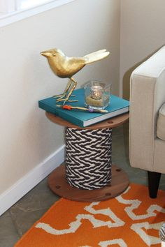 Electrical wire spool from Home Depot stained and wrapped with a cool rug to become a side table!
