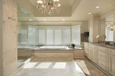 Bathroom featuring high ceiling with chandelier, glass shower area attached to bath, tile flooring and beige cabinetry.
