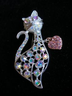 Hi there and welcome to in the magpies nest  For sale today is a completely gorgeous vintage brooch/pin. It is shaped like a pussy cat and measures 6x2.5cms. It is made from silver tone metal and the heart dangle is gold tone. The pin and clasp are in good working order. The kitty is set with lots of sparkling iridescent crystals and the heart shaped dangle is set with pink crystals - so pretty and completely adorable!  Condition - good wearable vintage condition - (see pics)  Your brooc...