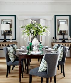The dining room of this sophisticated apartment is full of contradictions; a traditional, polished 'French Walnut' dining table has been unexpectedly paired with comfortable, curved chairs more usually associated with casual dining. Similarly, large classic pieces of furniture are counterbalanced by contemporary accessories, resulting in the perfect setting for formal yet relaxed dining. #manhattan #oka #diningroom