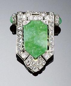 JADEITE AND DIAMOND DRESS CLIP. Of cartouche design set to the centre with a floral and foliate carved jadeite plaque within a surround of single- and rose-cut diamonds to cabochon jadeite terminals, signed Lacloche F and numbered, French assay marks.