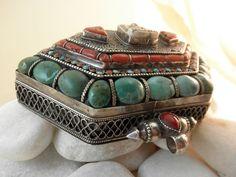 """""""Ga,u"""" Colgante tibetano de plata de ley,  turquesas  y corales naturales.  Esta joya tradicional tibetana forma una caja para llevar objetos de culto.  En la parte posterior de la tapa de la caja hay dos dorjes alrededor de un coral en el centro.  El dorje simboliza la dualidad entre las dos formas de la verdad, la relativa y la absoluta. Al girar, aparece en el centro, la realidad del momento presente.  Alto 114 mm.  Ancho 134 mm.  Peso 8oo gr.  Precio: 450 Euros"""