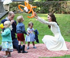 The Duchess of Cambridge lifts George's balloon creation over his head as William attempts to blow up another