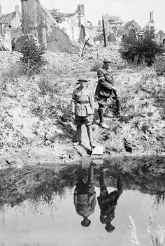 WWI, July 1916;     A 17' shell hole in the Main Square, Ypres. Brig.-Gen. Burstall and Captain Papineau. Cropped.   MIKAN no.  3403747