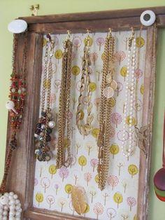 Colares pendurados em ganchinhos e em puxadores antigos.
