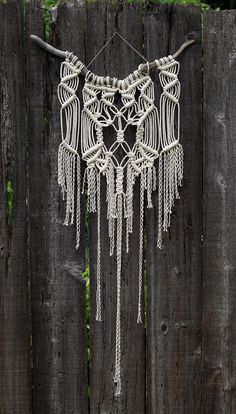 White macramé wall hanging on drift wood