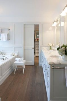 I like how wood floors warm up an otherwise white bathroom.  White cabinets, white granite countertops, white walls, chrome fixtures, flowers.