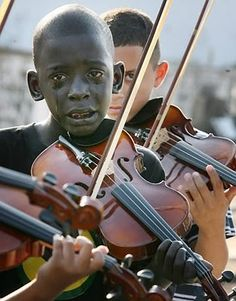 A boy weeps while playing at his violin teacher's funeral.