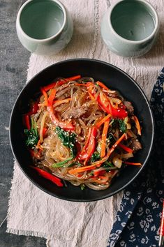Japchae is a simple Korean noodle dish packed with a rainbow of vegetables and steak. It's an easy, delicious, and light dish that's also gluten-free! source: thewoksoflife.com Korean Sweet Potato Noodles, Korean Glass Noodles, Easy Korean Recipes, Asian Recipes, Ethnic Recipes, Japchae Noodles, Wok Of Life, Korean Food, Korean Dishes