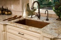 Warm taupes granite kitchen countertop and copper sink.